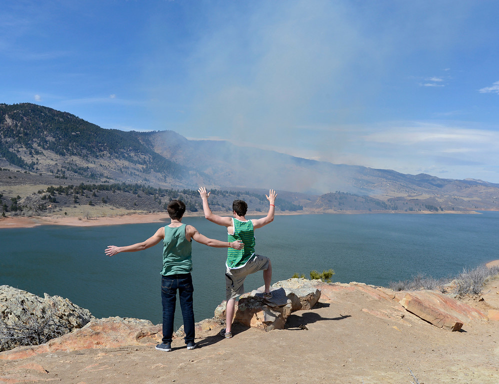 . Zach Alvarez, 18, left, and Tyler Webb, 17, hold their arms out against huge wind gusts as they watch smoke from the Soldier Canyon fire from the east side of Horsetooth Reservoir in Fort Collins on Friday, March 16, 2013. The two saw the smoke from Rocky Mountain High School and came up to get a closer look. Jenny Sparks, Loveland Reporter-Herald