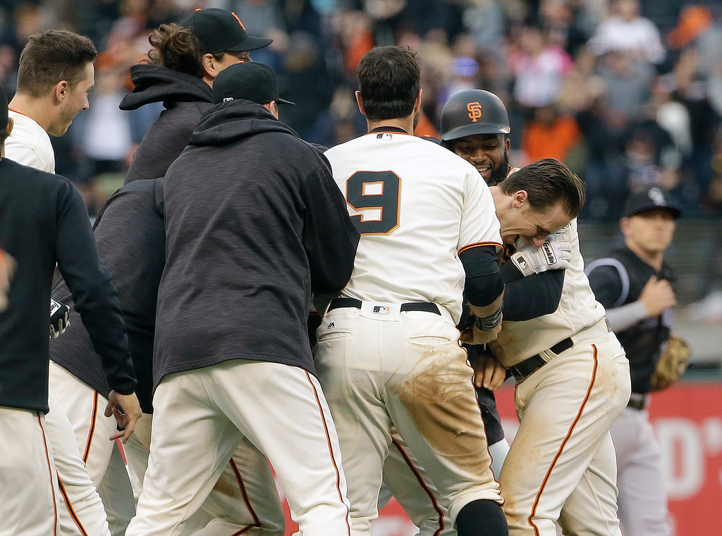 . San Francisco Giants\' Matt Duffy, facing right, is congratulated by teammates after doubling to score Conor Gillaspie for the winning run against the Colorado Rockies during the thirteenth inning of a baseball game in San Francisco, Saturday, May 7, 2016. The Giants won 2-1. (AP Photo/Jeff Chiu)