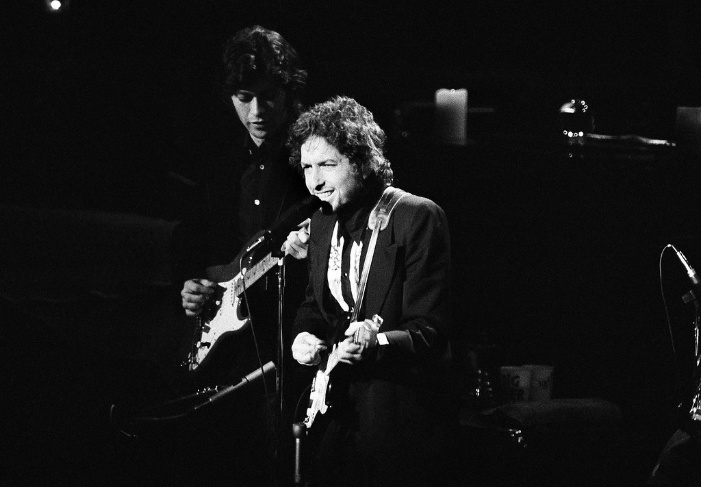 . Singer Bob Dylan leans towards the mike at New York\'s Madison Square Garden Jan. 30, 1974 during one of three appearances with The Band in New York City. Robbie Robertson, left, accompanies Dylan on guitar. (AP Photo/Ray Stubblebine)