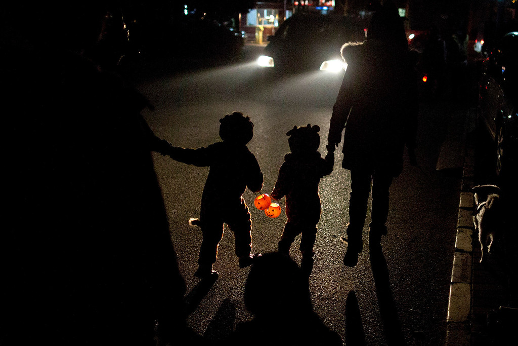 . Two children dressed in their Halloween costumes hold pumpkin-shaped lanterns while walking on their way to ask for candies from neighbors the night before Halloween in Beijing, China, Wednesday, Oct. 30, 2013. (AP Photo/Alexander F. Yuan)
