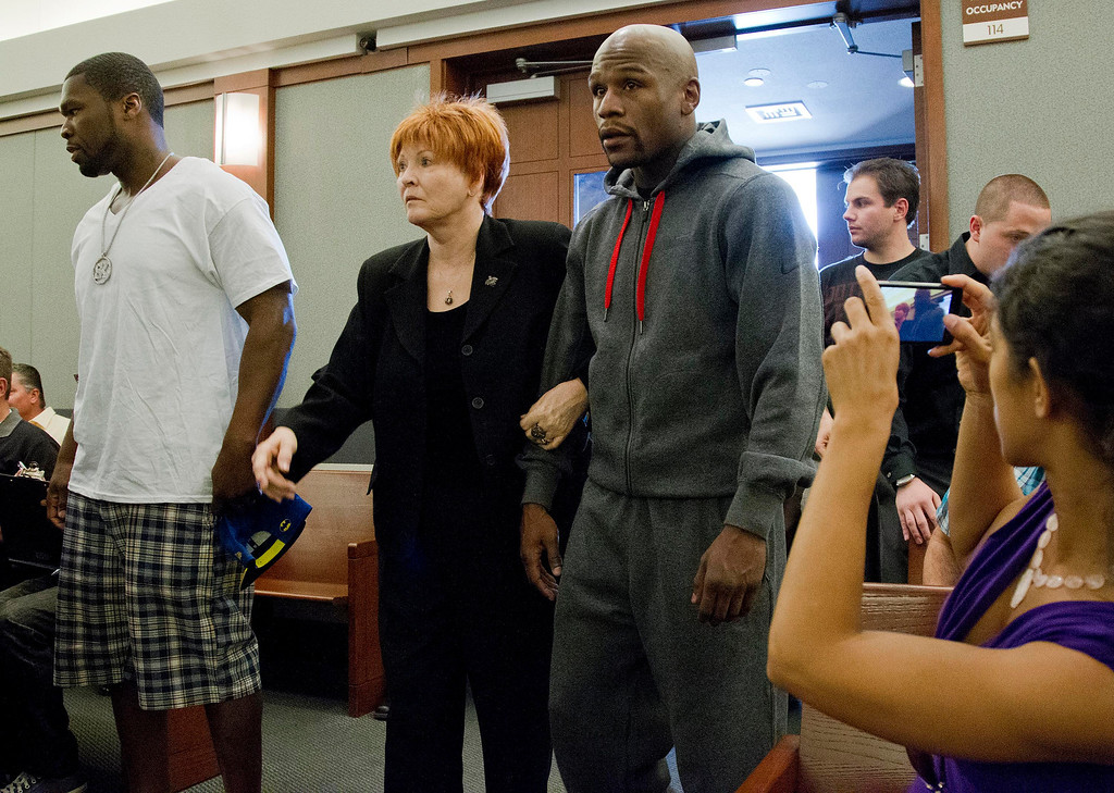. Floyd Mayweather Jr., right, walks into court escorted by his attorney Karen Winckler, center, and 50 Cent, left, to begin his 90-day jail term, Friday, June 1, 2012, in Las Vegas. The undefeated five-division champion surrendered Friday before the judge who sentenced him in December for attacking his ex-girlfriend in September 2010 while two of their children watched. (AP Photo/Julie Jacobson)