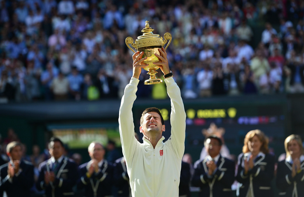 . Serbia\'s Novak Djokovic holds the winner\'s trophy after beating Switzerland\'s Roger Federer in the men\'s singles final match during the presentation on day thirteen of  the 2014 Wimbledon Championships at The All England Tennis Club in Wimbledon, southwest London, on July 6, 2014. Djokovic won his second Wimbledon title and seventh career major with a 6-7 (7/9), 6-4, 7-6 (7/4), 5-7, 6-4 victory over Roger Federer Sunday, shattering the Swiss star\'s dream of a record eighth triumph in a titanic struggle.  CARL COURT/AFP/Getty Images