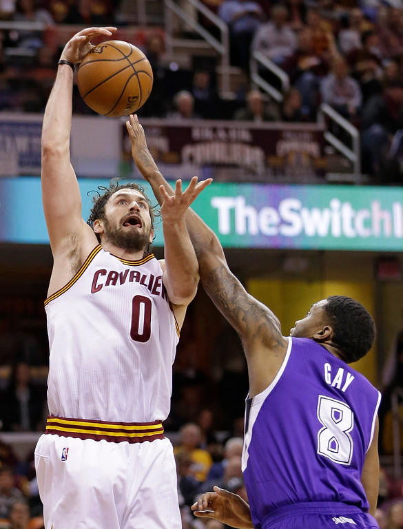 . Cleveland Cavaliers\' Kevin Love (0) is fouled by Sacramento Kings\' Rudy Gay (8) in the first half of an NBA basketball game Monday, Feb. 8, 2016, in Cleveland. (AP Photo/Tony Dejak)