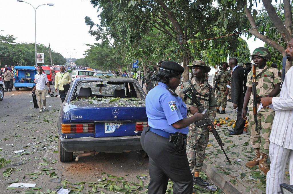 . Nigerian troops, right,  stand at the scene of an explosion in Abuja, Nigeria, Wednesday, June 25, 2014.  (AP Photo/Olamikan Gbemiga)