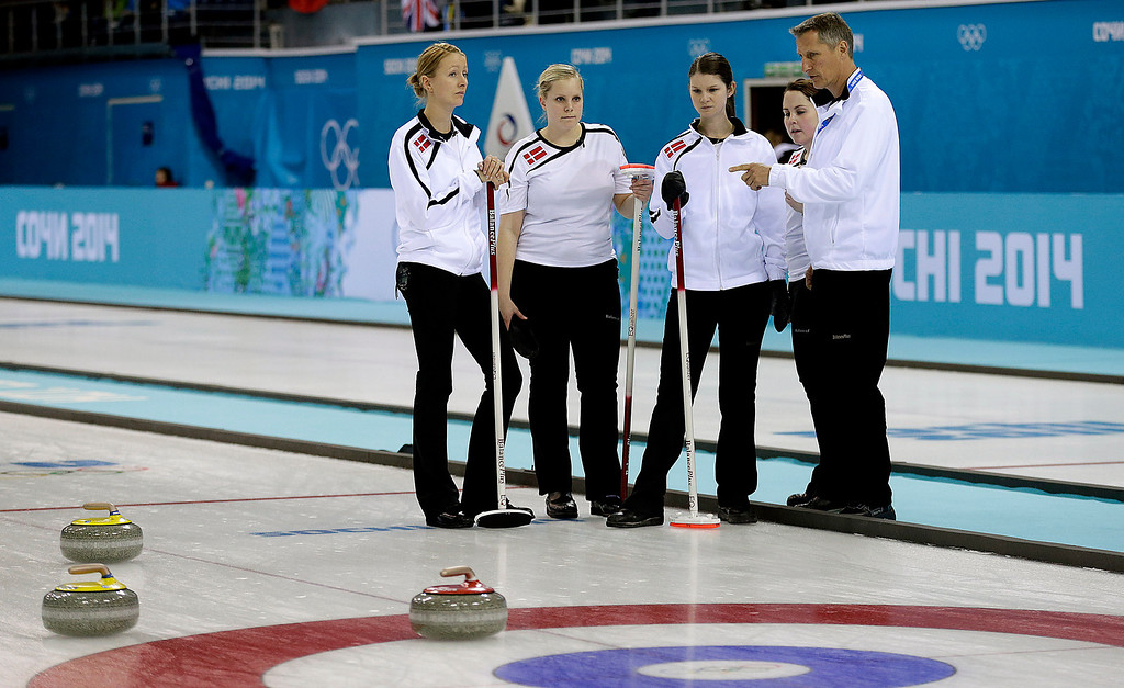 . Danish women\'s curling team from left to right, Helle Simonsen, Jeanne Ellegaard, Lene Nielsen and Maria Poulsen, strategize with their coach Gert Larsen, during the women\'s curling competition against Canada at the 2014 Winter Olympics, Thursday, Feb. 13, 2014, in Sochi, Russia. (AP Photo/Wong Maye-E)