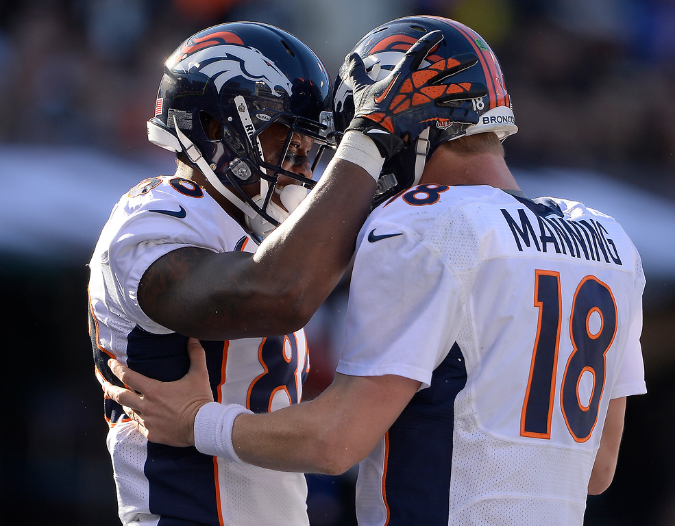 . Wide receiver Demaryius Thomas (88) and quarterback Peyton Manning (18) of the Denver Broncos celebrate a 63-yard touchdown pass during their game against the Oakland Raiders at O.co Coliseum on December 29, 2013 Oakland, Calif. During the game, Manning set a single-season passing yardage record with 5,477 passing yards. (Photo By Joe Amon/The Denver Post)