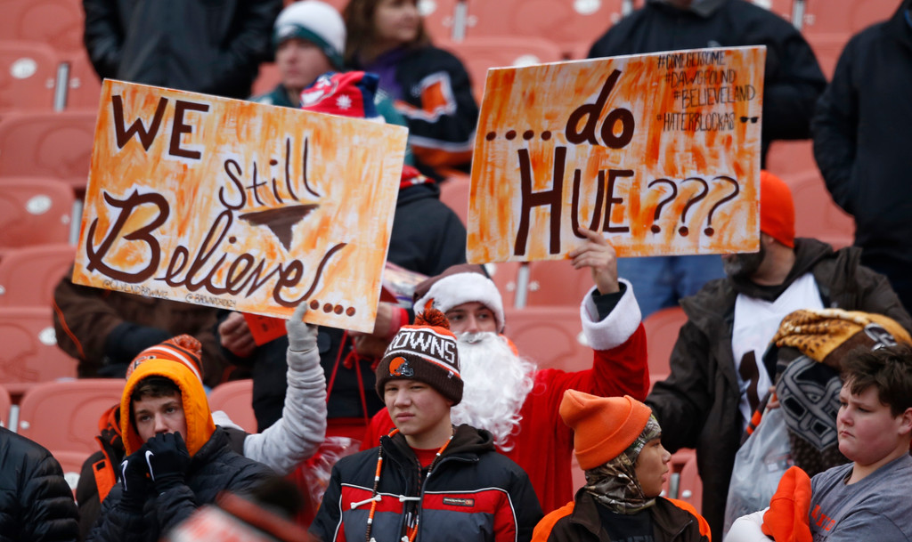 . Cleveland Browns fans hold up signs before an NFL football game between the Baltimore Ravens and the Cleveland Browns, Sunday, Dec. 17, 2017, in Cleveland. (AP Photo/Ron Schwane)