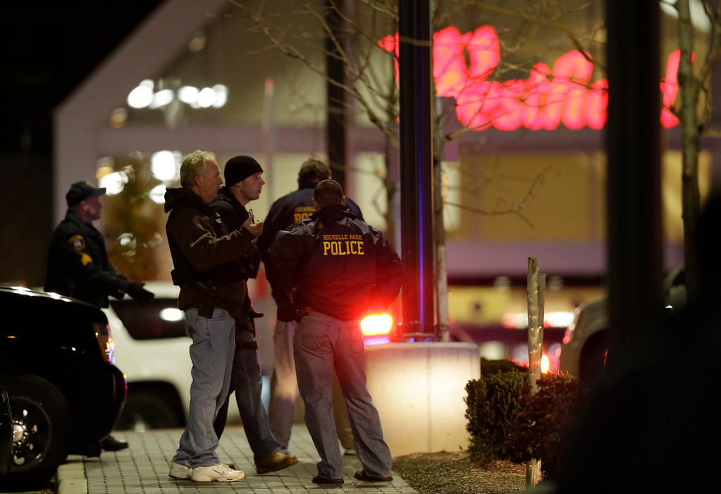 . Officials stand in the parking lot of the Garden State Plaza Mall following reports of a shooter, Monday, Nov. 4, 2013, in Paramus, N.J. Hundreds of law enforcement officers converged on the mall Monday night after witnesses said multiple shots were fired there. (AP Photo/Julio Cortez)