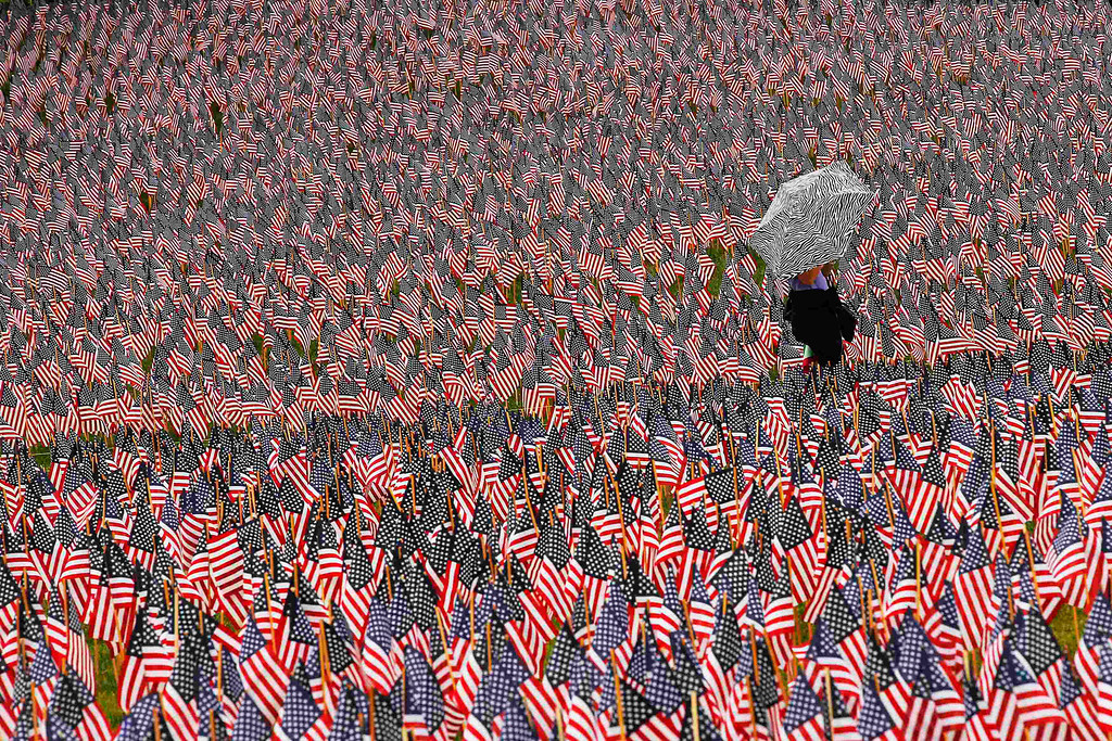 . A pedestrian carrying an umbrella walks through a Memorial Day display of United States flags on the Boston Common in Boston, Massachusetts May 23, 2013.  According to the Massachusetts Military Heroes Fund, the flags are planted on the Common for fallen Massachusetts service members at the Memorial Day holiday, which will be celebrated May 27 in the U.S.   REUTERS/Brian Snyder