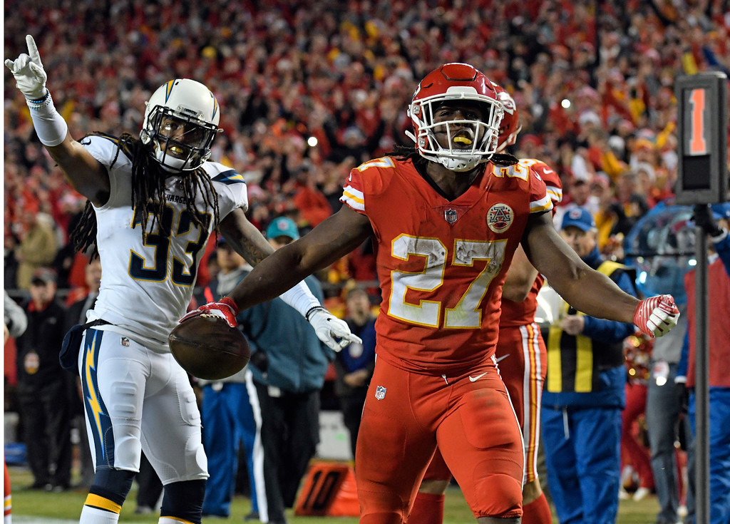 . Kansas City Chiefs running back Kareem Hunt (27) celebrates his touchdown in front of Los Angeles Chargers safety Tre Boston (33) during the second half of an NFL football game in Kansas City, Mo., Saturday, Dec. 16, 2017. (AP Photo/Ed Zurga)