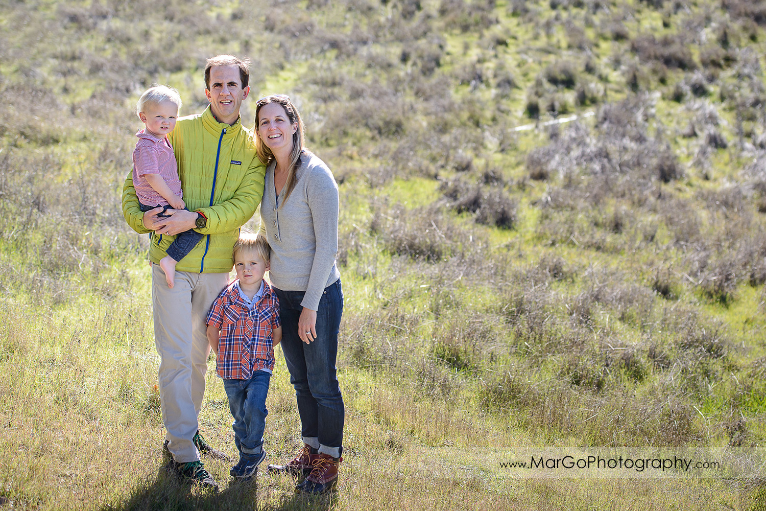 full body portrait of family of four standing in the grass and looking into camera at San Raeael China Camp SP