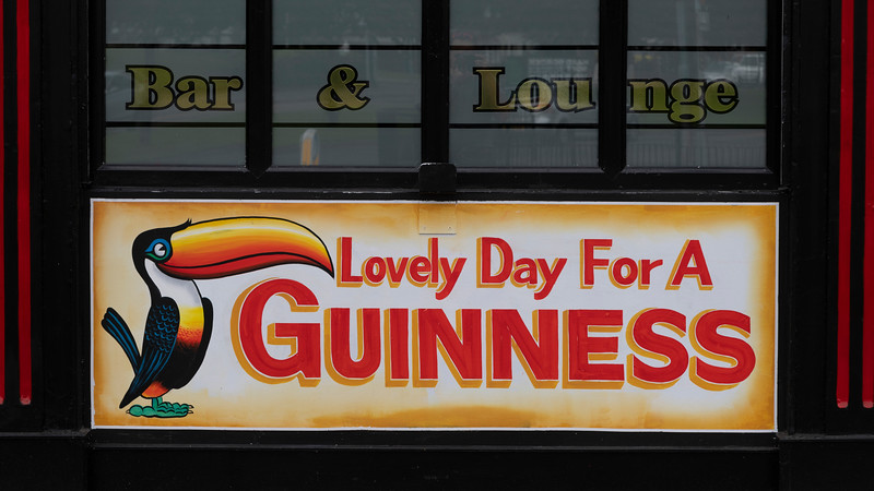 Close-up of 'Lovely Day for a Guinness' sign at bar, Free Derry, Londonderry, Northern Ireland, United Kingdom