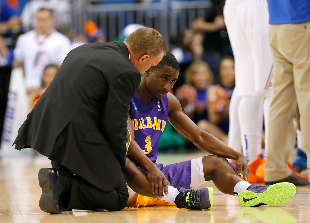 . ORLANDO, FL - MARCH 20:  DJ Evans #3 of the Albany Great Danes is checked on by a trainer after getting kneed unintentionally in the head while taking on the Florida Gators during the second round of the 2014 NCAA Men\'s Basketball Tournament at Amway Center on March 20, 2014 in Orlando, Florida.  (Photo by Kevin C. Cox/Getty Images)