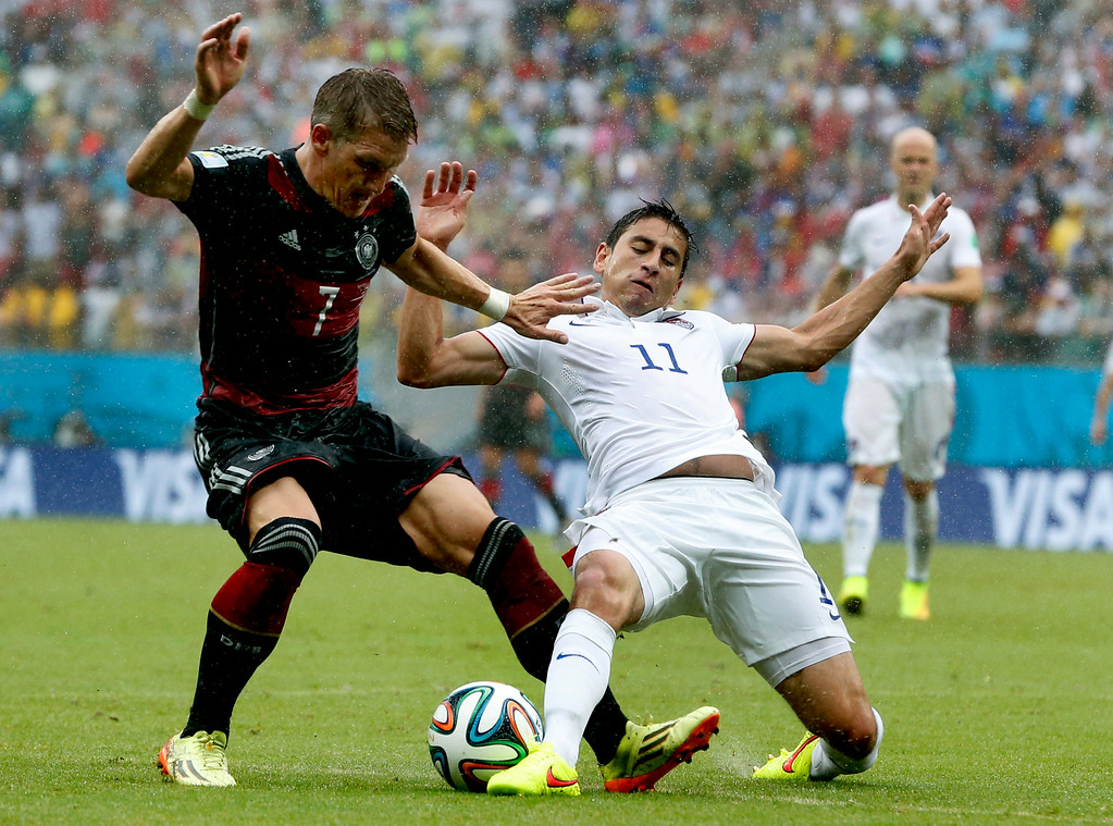 . Germany\'s Bastian Schweinsteiger, left, is challenged by United States\' Alejandro Bedoya, right, during the group G World Cup soccer match between the USA and Germany at the Arena Pernambuco in Recife, Brazil, Thursday, June 26, 2014. (AP Photo/Matthias Schrader)