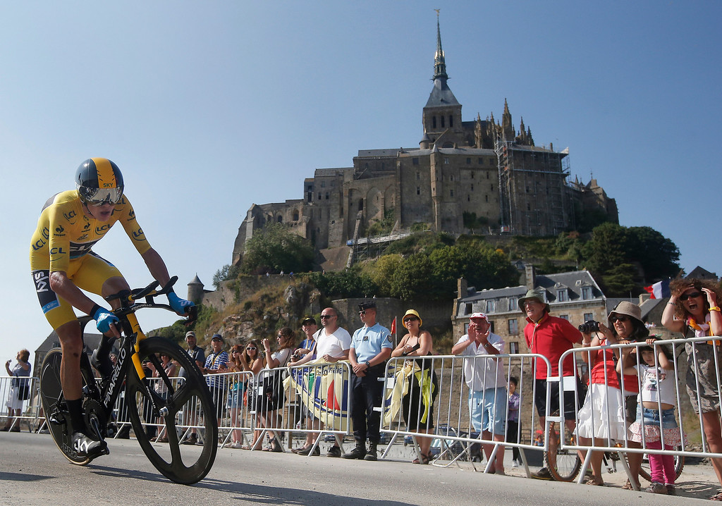 . Christopher Froome of Britain, wearing the overall leader\'s yellow jersey, passes world heritage site Mont-Saint-Michel, rear, a rocky tidal island which holds a monastery, during the eleventh stage of the Tour de France cycling race, an individual time trial over 33 kilometers (20.6 miles) with start in in Avranches and finish in Mont-Saint-Michel, western France, Wednesday July 10 2013. (AP Photo/Laurent Cipriani)