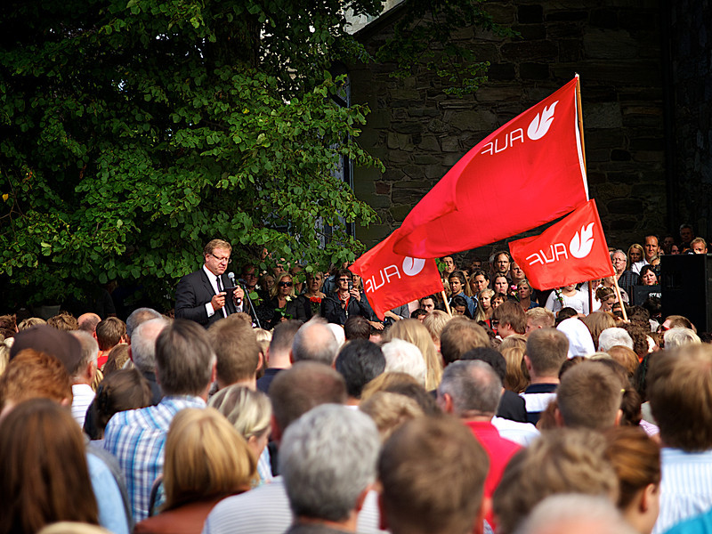 The red flags of the Labour Party Youth organization held high while the assembled people listen to Mayor Leif Johan Sevland. (Foto: Geir)
