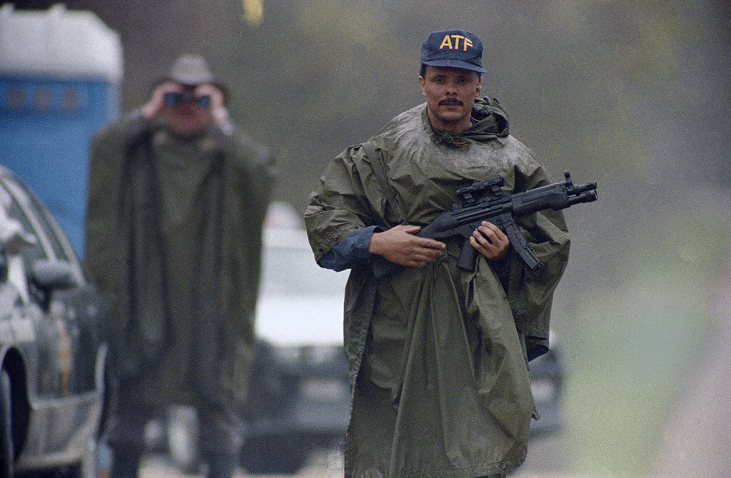 . An Alcohol, Tobacco and Firearms agent stands in the rain at a barricade north of the Branch Davidian compound near Waco, Texas on Monday, March 22, 1993.  (AP Photo/George Widman)