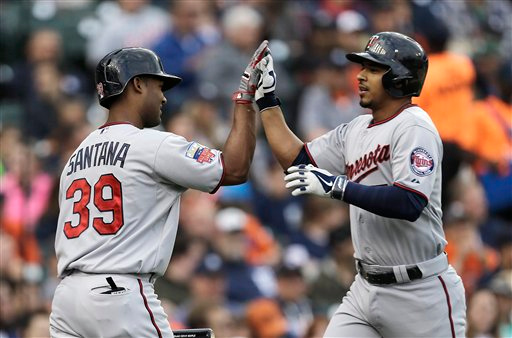 . Minnesota Twins\' Eduardo Escobar, right, is congratulated by Danny Santana after hitting a solo home run against the Detroit Tigers in the third inning of a baseball game in Detroit, Friday, June 13, 2014.  (AP Photo/Paul Sancya)
