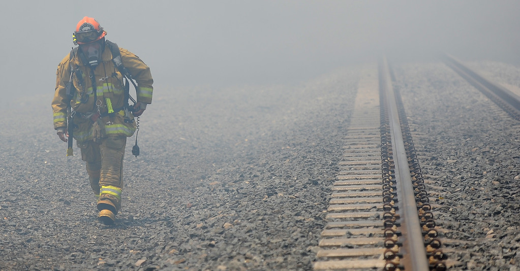 . Los Angeles County firefighter capt. walks through heavy smoke as they battle 3-alarm fire at an abandoned warehouse near 9th Avenue and Clark Avenue on Tuesday, July 9, 2013 in City of Industry, Calif.  (Keith Birmingham/Pasadena Star-News)