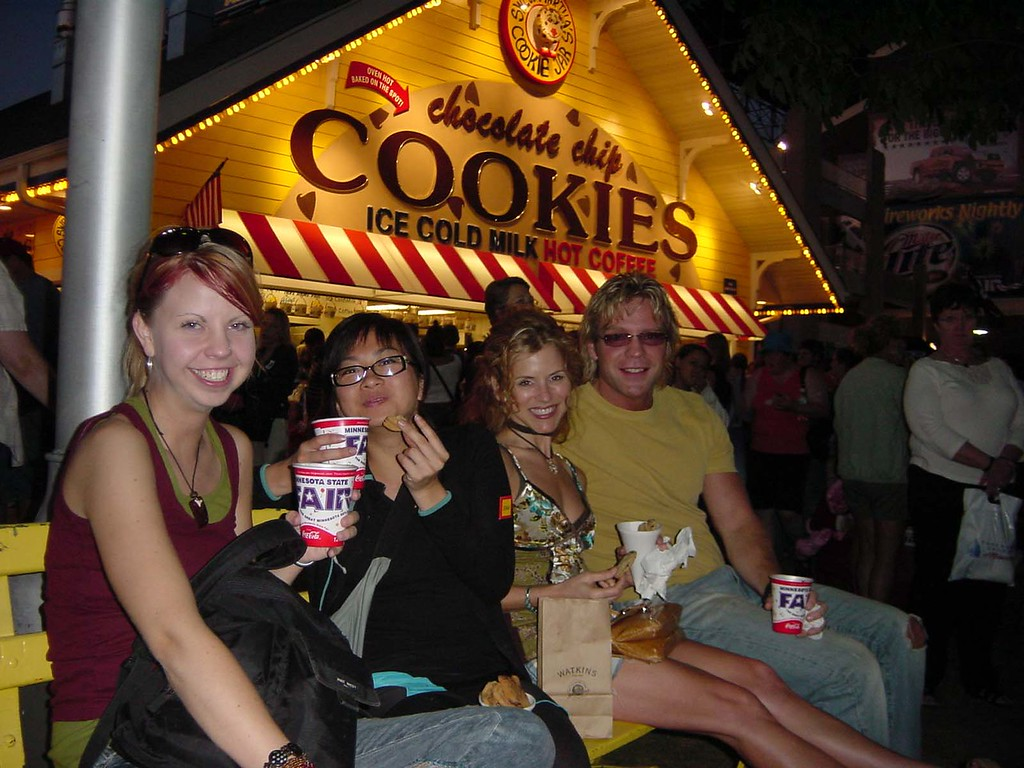 . People sit on a bench, enjoying Sweet Martha\'s Cookies at night during the 2005 Minnesota State Fair. Photo courtesy of the Minnesota State Fair.
