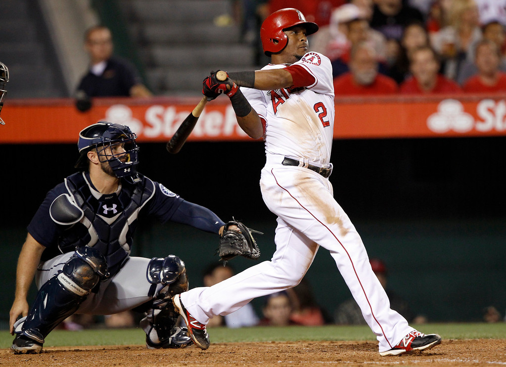 . Los Angeles Angels\' Erick Aybar (2) hits a double to center field with Seattle Mariners catcher Kelly Shoppach, left, looking on in the fourth inning during a baseball game Tuesday, May 21, 2013 in Anaheim.    (AP Photo/Alex Gallardo)