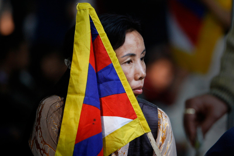 . An exiled Tibetan woman holds a Tibetan flag during a rally to mark World Human Rights Day in New Delhi, India, Monday, Dec. 10, 2012. At least 86 people have set themselves on fire since 2009. Tibetans also mark Dec. 10 as Nobel Peace Prize Day, the day the Dalai Lama received the Nobel peace prize in 1989. (AP Photo/Tsering Topgyal)