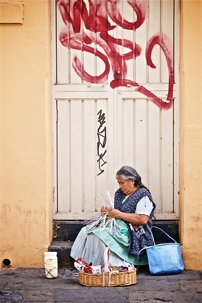 A woman sits in a doorway weaving a basket in Oaxaca, Mexico.