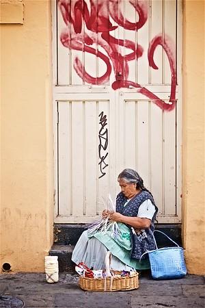 A woman sits in a doorway weaving a basket in Oaxaca, Mexico.