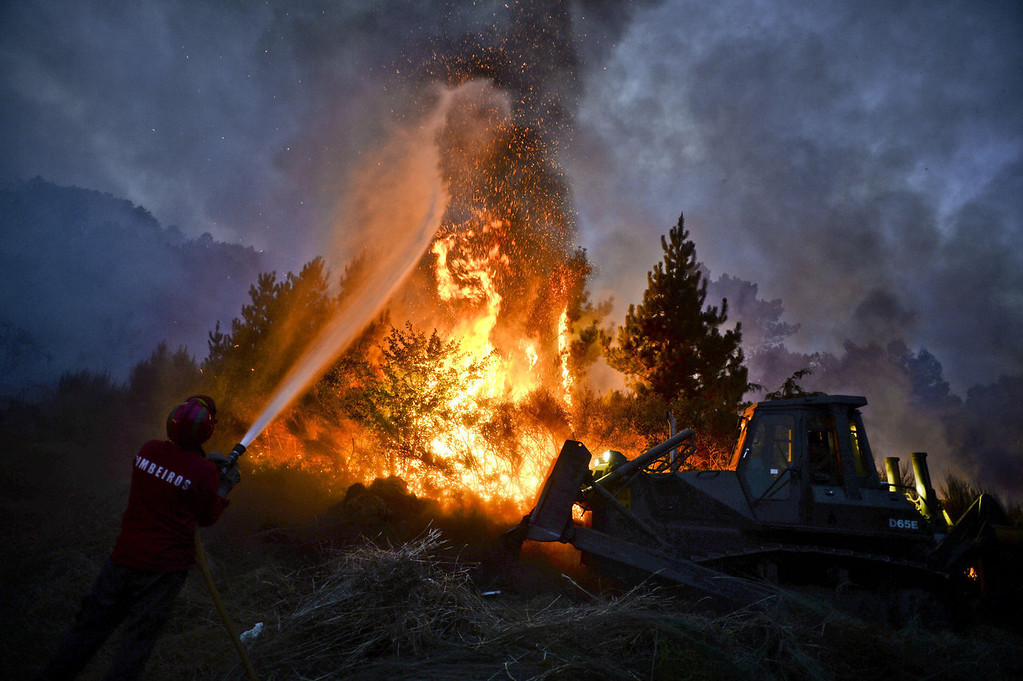 . A firefighter uses a hose as a bulldozer pushes earth onto a wildfire in Caramulo, central Portugal on August 29, 2013. Five Portuguese mountain villages were evacuated overnight as forest fires intensified in the country\'s north and centre, officials said today. As many as 1,400 firefighters were dispatched Thursday to tackle the blaze in the mountains and another raging further north in the national park of Alvao, where 2,000 hectares (4,900 acres) of pine forest have already been destroyed, according to the local mayor.   PATRICIA DE MELO MOREIRA/AFP/Getty Images