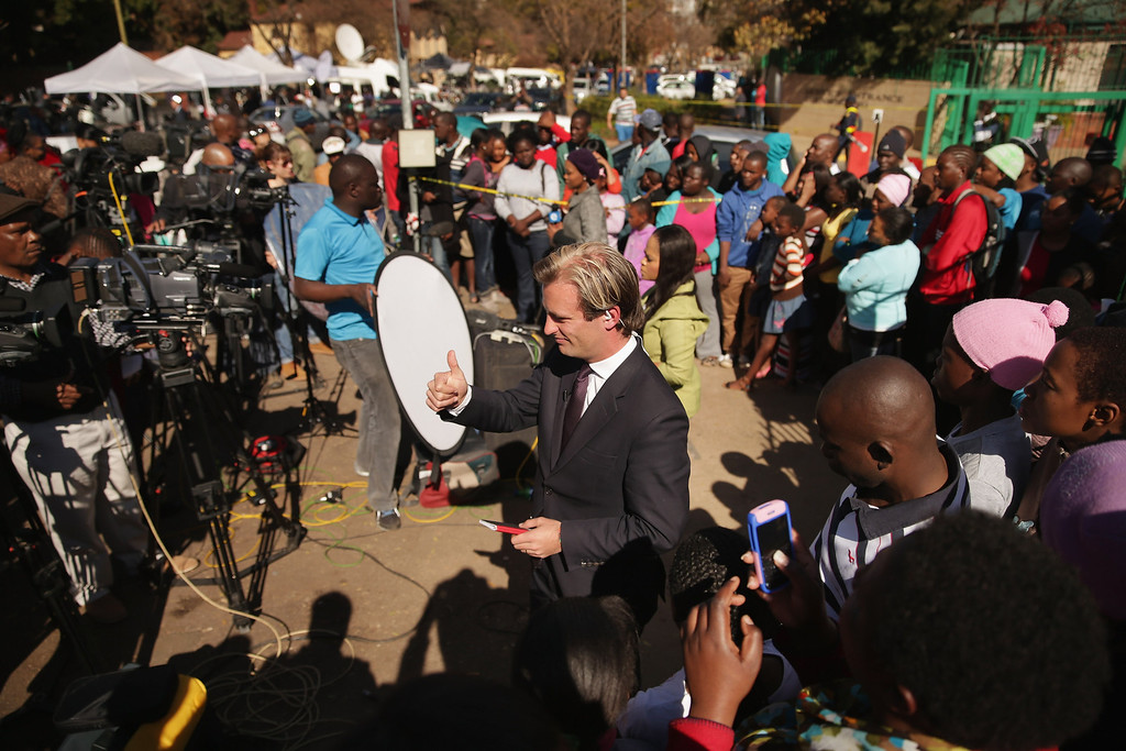 . PRETORIA, SOUTH AFRICA - JUNE 25:  A crowd gathers to watch television news reporters outside of the Mediclinic Heart Hospital where former South African President Nelson Mandela is being treated June 25, 2013 in Pretoria, South Africa. South African President Jacob Zuma confirmed Sunday that Mandela\'s condition has become critical since he was admitted to the hospital over two weeks ago for a recurring lung infection.  (Photo by Chip Somodevilla/Getty Images)