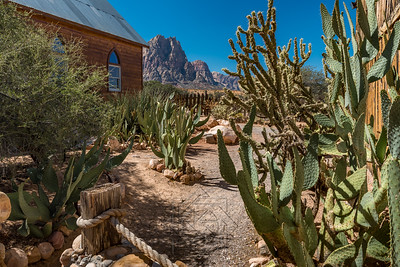 Courtyard next to a wooden church with desert cacti