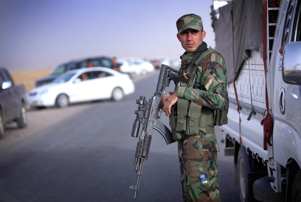 . An Iraqi Kurdish security guard (Peshmerger)  stands guard as Iraqi families fleeing violence in the northern Nineveh province gather at a Kurdish checkpoint in Aski kalak, 40 kms West of Arbil, in the autonomous Kurdistan region, on June 11, 2014. Since the Islamic State of Iraq and the Levant (ISIL) began their spectacular assault in Mosul late on June 9, militants have captured a large swathe of northern and north-central Iraq, prompting as many as half a million people to flee their homes. SAFIN HAMED/AFP/Getty Images
