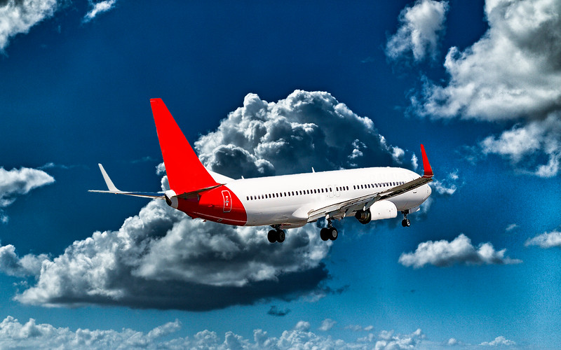 Aircraft in flight with cumulonimbus cloud in blue sky. Queensland.