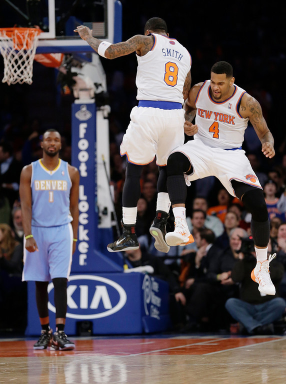 . New York Knicks\' Jeremy Tyler (4) celebrates with teammate J.R. Smith (8) after scoring on an assist from Smith during the second half of an NBA basketball game against the Denver Nuggets on Friday, Feb. 7, 2014, in New York. The Knicks won 117-90. (AP Photo/Frank Franklin II)