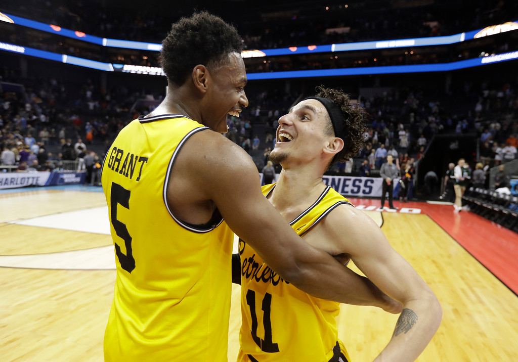 . UMBC\'s K.J. Maura (11) and Jourdan Grant (5) celebrate the team\'s 74-54 win over Virginia in a first-round game in the NCAA men\'s college basketball tournament in Charlotte, N.C., Friday, March 16, 2018. (AP Photo/Gerry Broome)