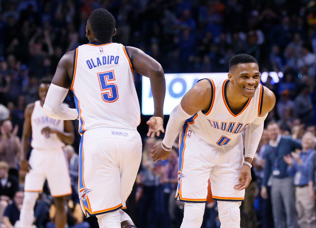 . Oklahoma City Thunder guard Russell Westbrook (0) slaps hands with teammate Victor Oladipo (5) following Oladipo\'s basket that gave Westbrook his 10th assist and clinched his triple-double, during the fourth quarter of the team\'s NBA basketball game against the Cleveland Cavaliers in Oklahoma City, Thursday, Feb. 9, 2017. Oklahoma City won 118-109. (AP Photo/Sue Ogrocki)