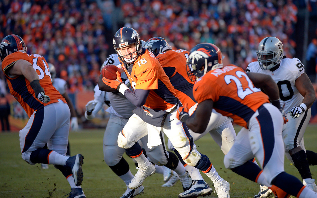 . DENVER, CO - DECEMBER 28: Peyton Manning (18) of the Denver Broncos hands off to C.J. Anderson (22) of the Denver Broncos during the second quarter.  No gain on the play.  The Denver Broncos played the Oakland Raiders at Sports Authority Field at Mile High in Denver on December, 28 2014. (Photo by Joe Amon/The Denver Post)
