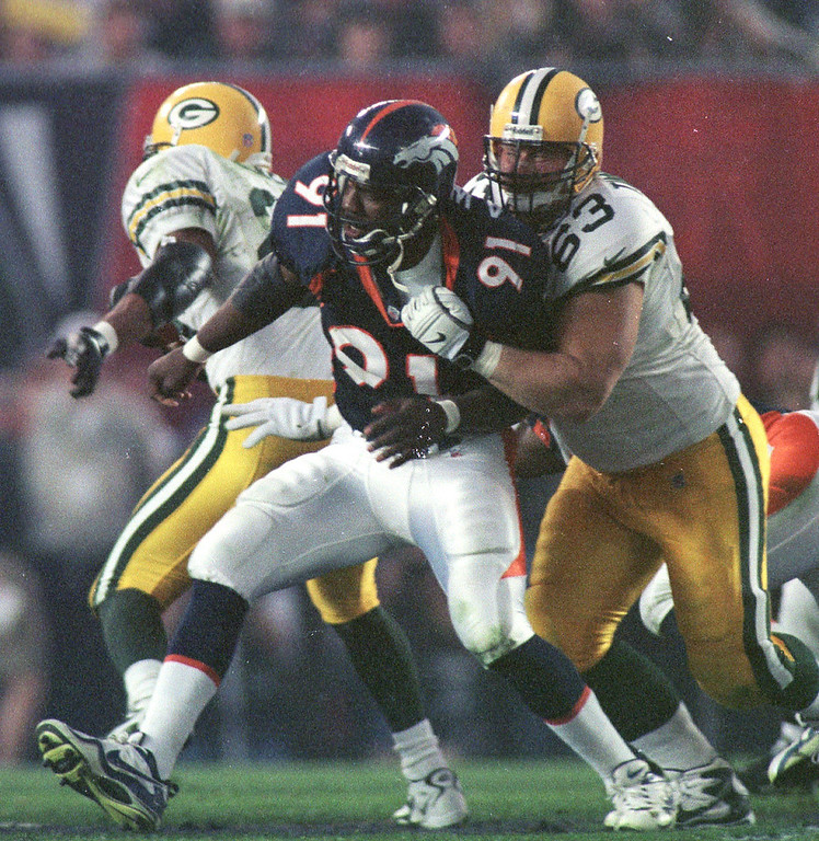 . Caption: Denver Broncos Alfred Williams is held by Green Bay  Packers Adam Timmerman during Super Bowl XXXII in San Diego CA.     (Karl Gehring/The Denver Post)