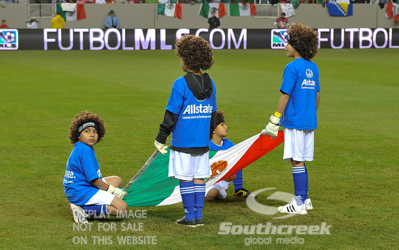Young boys hold the Mexico flag  during pre-game ceremonies before Soccer action between Bosnia-Herzegovina and Mexico.  Mexico defeated Bosnia-Herzegovina 2-0 in the game at the Georgia Dome in Atlanta, GA.