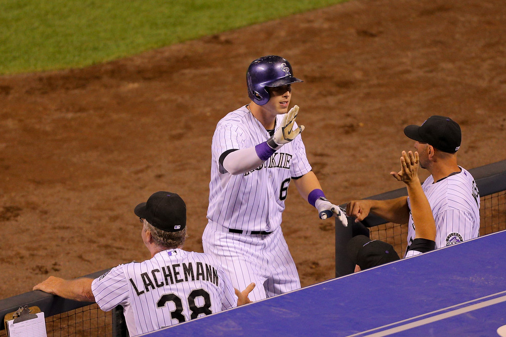 . DENVER, CO - SEPTEMBER 16:  Corey Dickerson #6 of the Colorado Rockies celebrates at the top of the dugout after hitting a two-run home run during the fourth inning against the Los Angeles Dodgers at Coors Field on September 16, 2014 in Denver, Colorado. (Photo by Justin Edmonds/Getty Images)