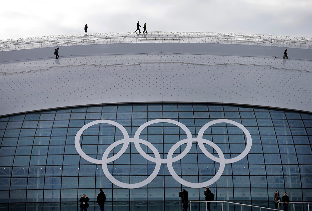 . Workers walk on the roof of the Bolshoy Ice Dome, which is the venue for the ice hockey matches, ahead of the 2014 Winter Olympics, Tuesday, Feb. 4, 2014, in Sochi, Russia. (AP Photo/Wong Maye-E)