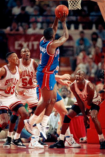 Description of . Chicago Bulls' Michael Jordan, right, shouts as Detroit Pistons' Joe Dumars goes up for a shot during second half action in Chicago, June 2, 1990.  Chicago's Scottie Pippen, left, and Horace Grant (54) watch. The Bulls won, 109-91 and evened the best-of-seven series at three games. (AP Photo/Mark Elias)