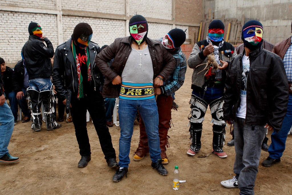 ". Masked fighter Eber Sabina, center, is helped by friends with his outfit before entering a Takanakuy ritual fight in Lima, Peru. The fighters dress up in costumes of Andean folklore figures, with the ski masks an integral part of the costume. Among the characters: ""El Negro,\"" representative of black slaves; \""El Majeno,\"" reminiscent of liquor salesmen from a region called Majes; and \""El Gallo,\"" the rooster. (AP Photo/Karel Navarro)"