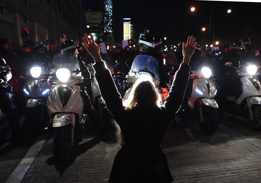 . A protestor hold up her hands in front of the NYPD  as she and others block traffic on the West Side Highway during demonstrations December 4, 2014 in  New York City against the chokehold death of an unarmed black father-of-six by a white police officer.   It is the second consecutive night that demonstrators took to the streets of New York to condemn a grand jury\'s decision not to indict the officer over the July 17 death of Eric Garner.  AFP PHOTO / Timothy A. CLARY/AFP/Getty Images