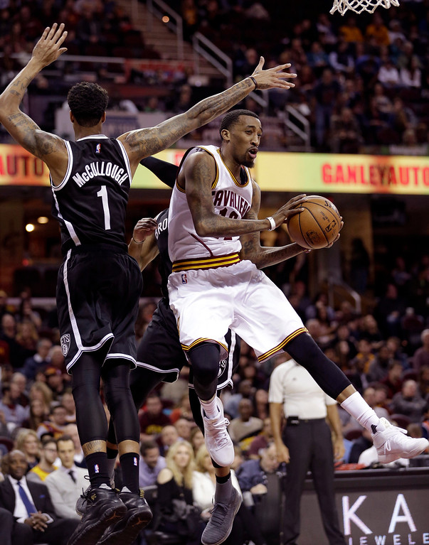 . Cleveland Cavaliers\' Jordan McRae, right, looks to pass against Brooklyn Nets\' Chris McCullough in the second half of an NBA basketball game, Friday, Dec. 23, 2016, in Cleveland. (AP Photo/Tony Dejak)