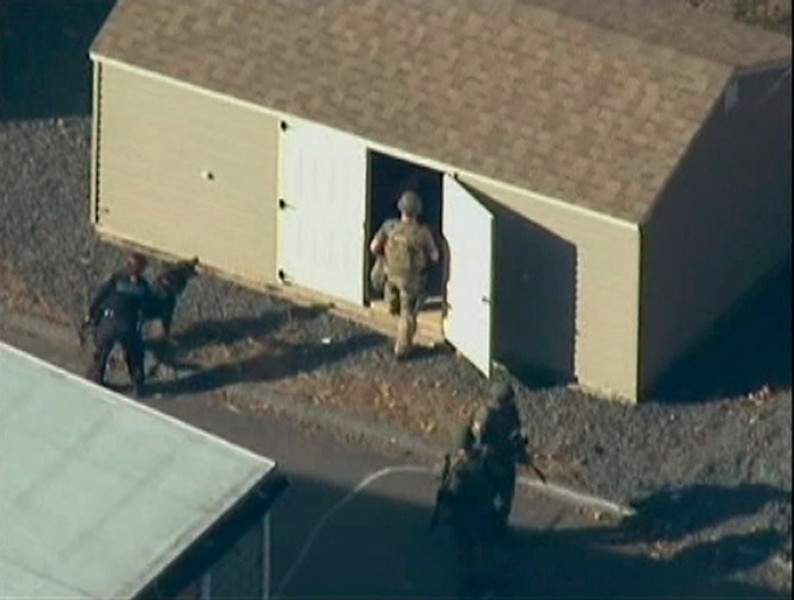 . Police search a building after a shooting at Sandy Hook Elementary School in Newtown, Connecticut, December 14, 2012.  REUTERS/WNBC/Handout