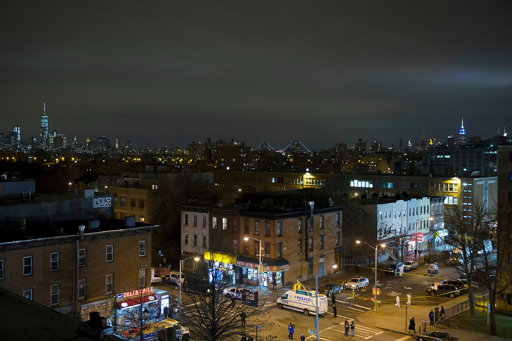 . The skyline of Manhattan is seen in the background as investigators work at the scene where two NYPD officers were shot, Saturday, Dec. 20, 2014 in the Bedford-Stuyvesant neighborhood of the Brooklyn borough of New York. Police said an armed man walked up to two officers sitting inside the patrol car and opened fire before running into a nearby subway station and committing suicide. Both police officers were killed. (AP Photo/John Minchillo)