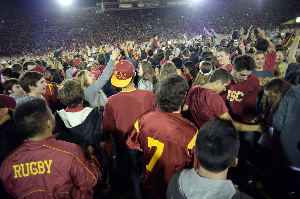. USC fans storm the field after defeating Stanford during their game at the Los Angeles Memorial Coliseum Saturday, November 16, 2013. USC beat Stanford 20-17. (Photos by Hans Gutknecht/Los Angeles Daily News)