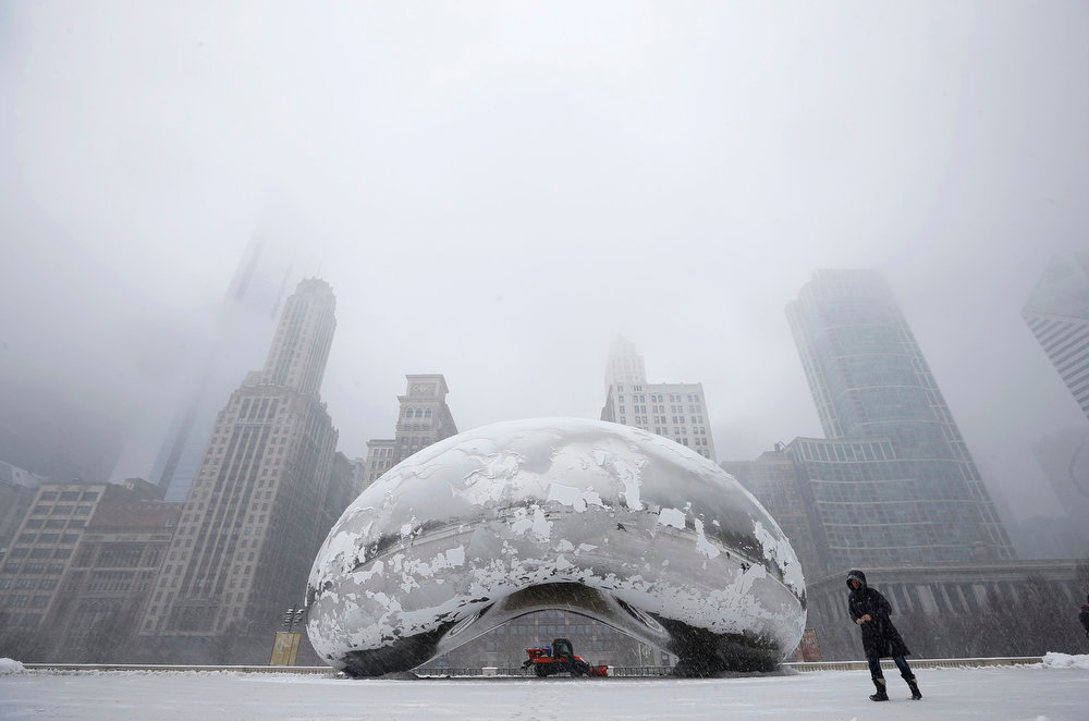 ". A woman walks by the Cloud Gate Sculpture, known as ""The Bean\"", as a snow plow clears the area during a snowstorm in Chicago March 5, 2013. A deadly late winter storm dumped heavy snow on the Midwestern United States on Tuesday, contributing to numerous highway crashes and flight cancellations as it moved east toward the Ohio Valley and the mid-Atlantic states.  REUTERS/Jim Young"