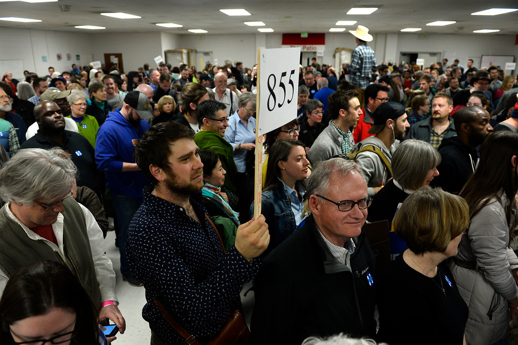 . Will Schultz holds up his precinct sign as he leads his members towards rooms at East High school  in Denver, Colorado on March 1, 2016. 18 precincts were represented at East High School and thousands of people turned out for the caucus. Organizers had anticipated about 20% of people from their precincts would turn out and many more  actually came. (Photo by Helen H. Richardson/The Denver Post)